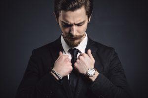 Мужчина в деловом стиле с часами и браслетом на руке